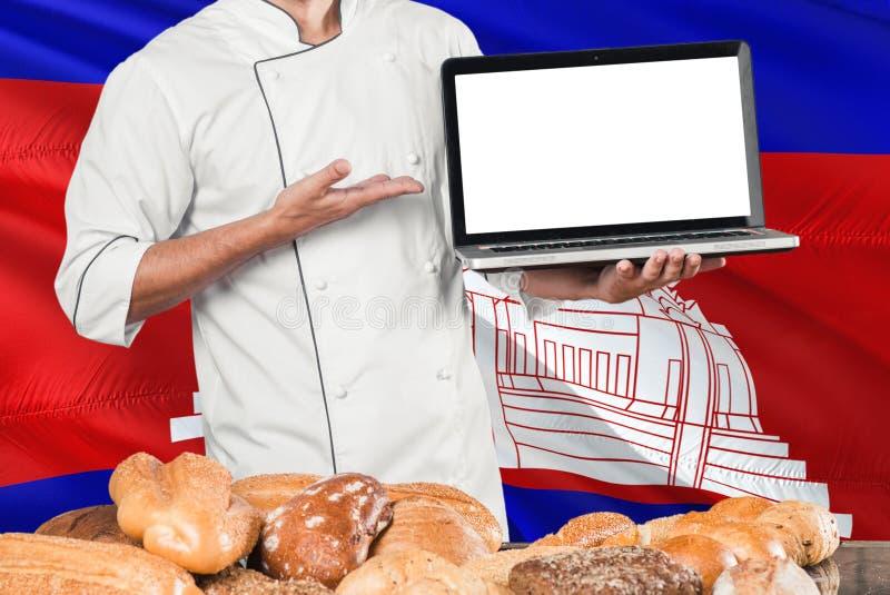 Ordenador portátil camboyano de la tenencia del panadero en la bandera de Camboya y el fondo de los panes Uniforme que lleva del  foto de archivo