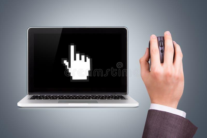 Ordenador portátil con el icono y mano que sostiene el ratón imagenes de archivo