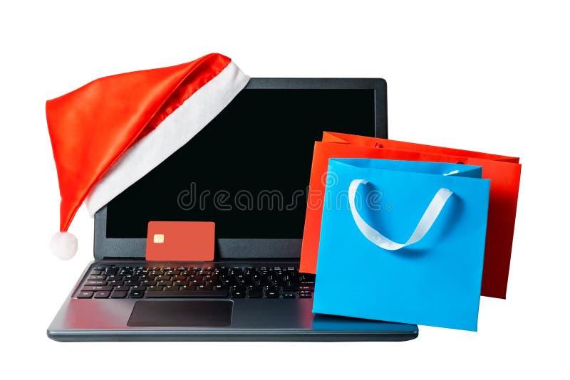 Ordenador portátil con el sombrero de santa, la tarjeta de crédito roja y los panieres aislados fotografía de archivo