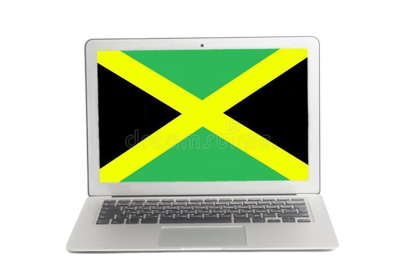 Ordenador portátil con la bandera de Jamaica en la pantalla foto de archivo libre de regalías