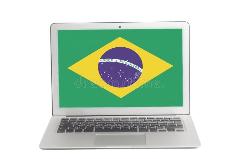 Ordenador portátil con la bandera del Brasil en la pantalla fotos de archivo