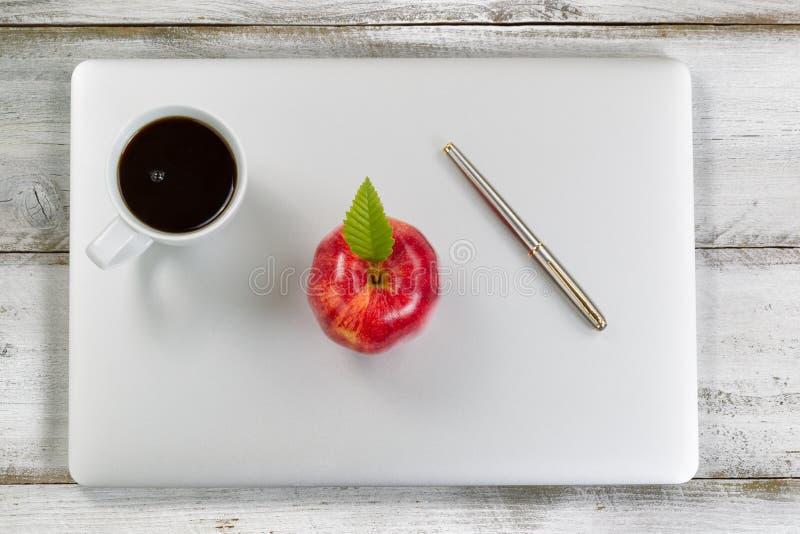 Ordenador portátil con la manzana y el café rojos frescos encima de la mesa vieja fotos de archivo libres de regalías