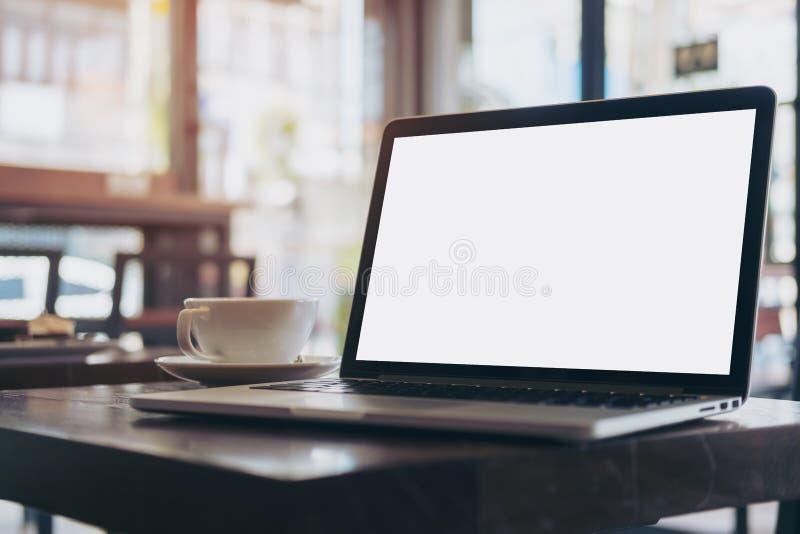 Ordenador portátil con la pantalla blanca en blanco en la tabla de madera en café moderno del desván fotos de archivo libres de regalías