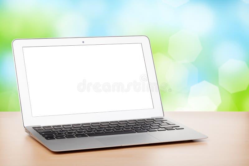 Ordenador portátil con la pantalla en blanco en la tabla fotografía de archivo