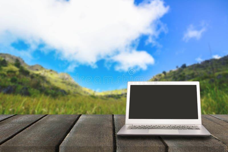 Ordenador portátil con la pantalla en blanco en la tabla de madera con el bosque en montaña fotos de archivo