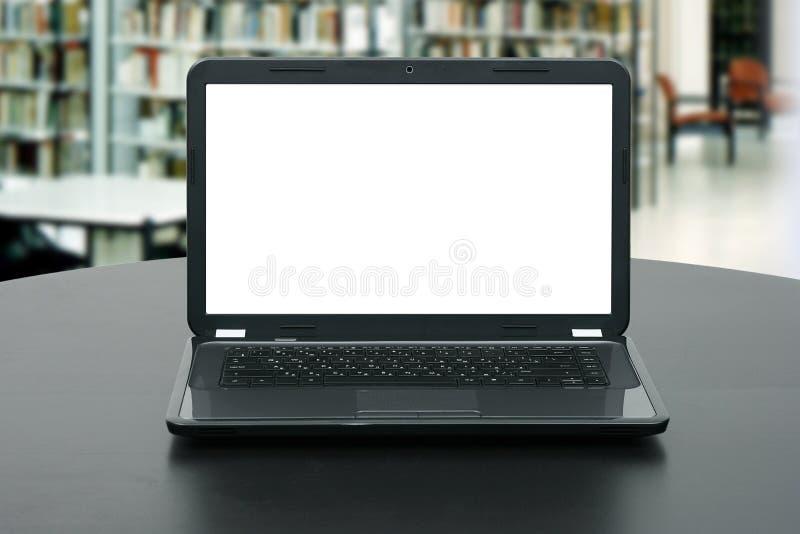 Ordenador portátil con la pantalla en blanco en la tabla en biblioteca fotografía de archivo libre de regalías
