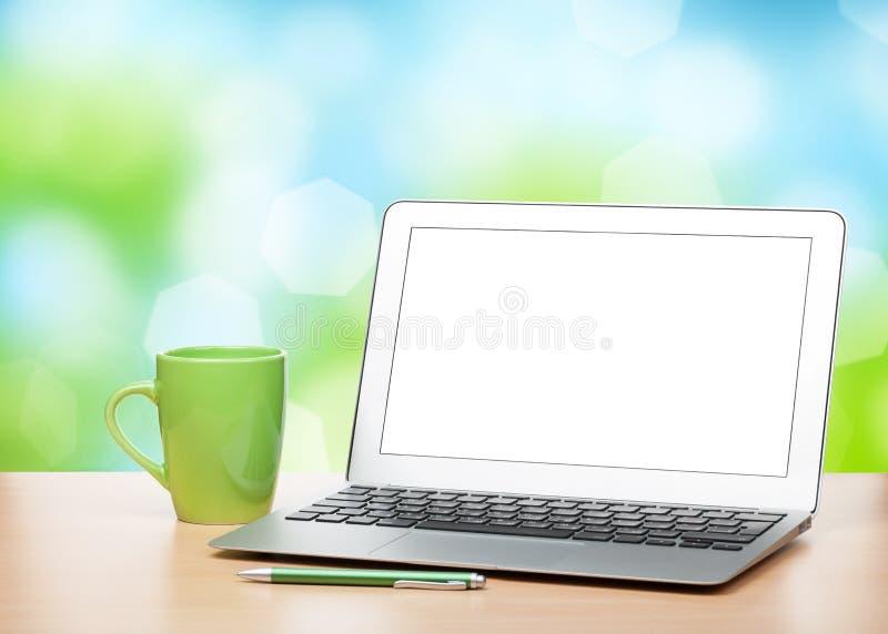 Ordenador portátil con la pantalla en blanco y la taza en la tabla imagenes de archivo