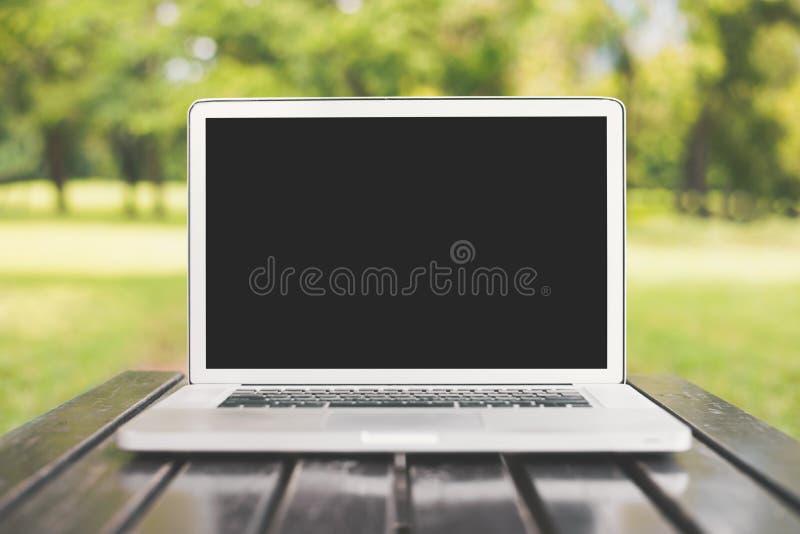Ordenador portátil con la pantalla negra en blanco en backgrou verde de la naturaleza fotografía de archivo libre de regalías