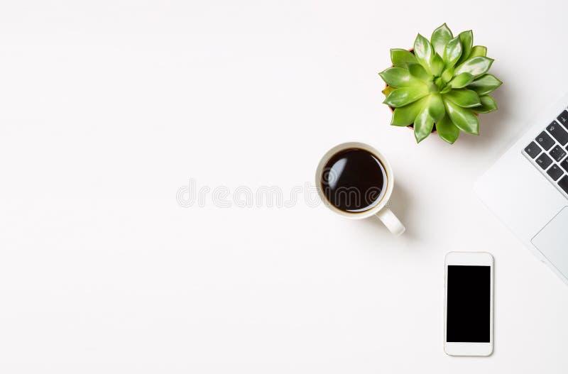 Ordenador portátil con la planta en un pote, la taza de café y el teléfono móvil moderno en el fondo blanco Espacio de trabajo co foto de archivo