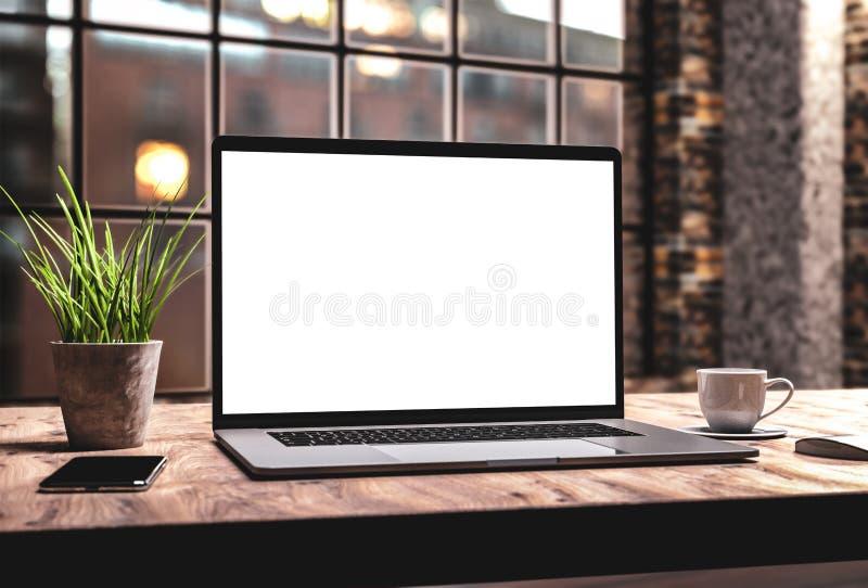 Ordenador portátil con la plantilla de la maqueta de la pantalla en blanco en la tabla en viejo interior industrial del desván de fotografía de archivo
