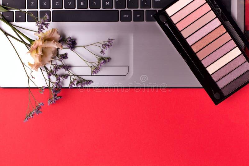 Ordenador portátil con las flores y los cosméticos en la tabla Espacio de trabajo del Freelancer imagen de archivo libre de regalías