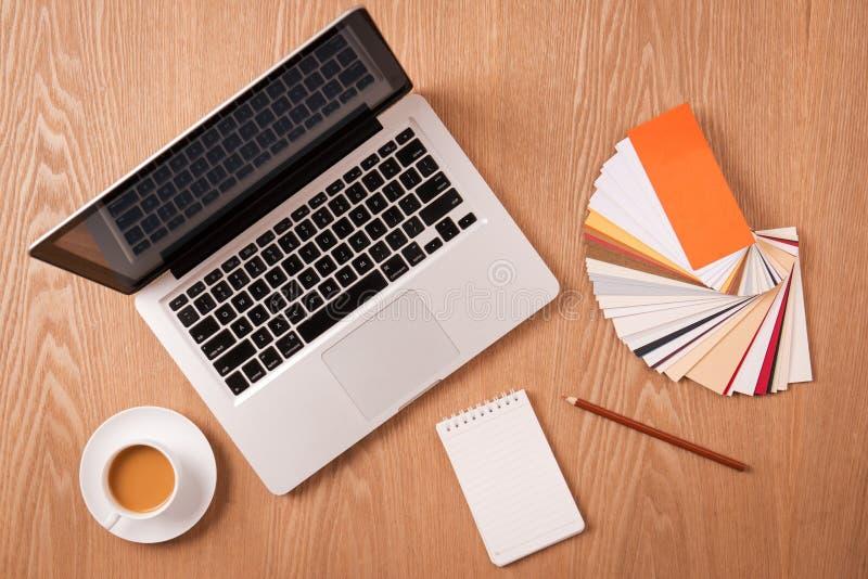 Ordenador portátil con muestras y materiales de oficina del color del diseñador fotos de archivo libres de regalías