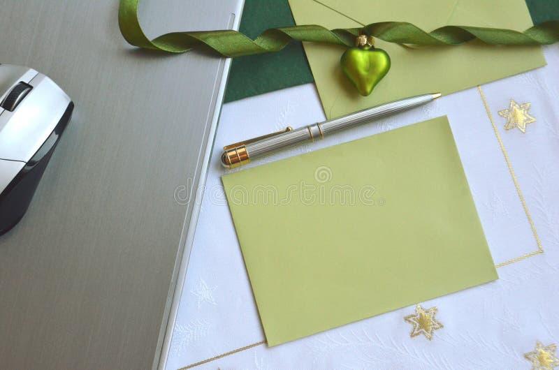 Ordenador portátil con una tarjeta de nota verde y un ornamento verde de la Navidad Disposición del Flt imagenes de archivo