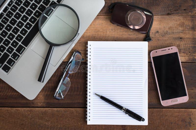 Ordenador portátil, cuaderno, smartphone, espectáculo, cámara y lupa en la tabla de madera foto de archivo