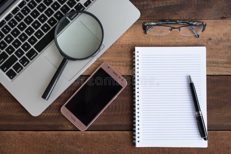 Ordenador portátil, cuaderno, smartphone, espectáculo y lupa en la tabla de madera foto de archivo libre de regalías