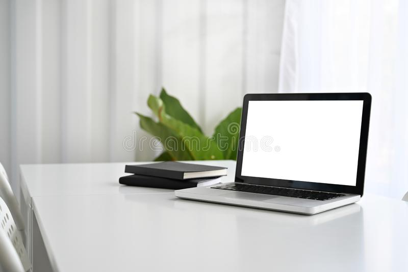 Ordenador portátil de la maqueta y documento del cuaderno sobre la tabla de funcionamiento fotos de archivo libres de regalías
