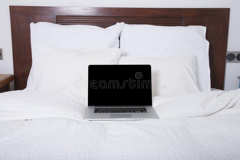 Ordenador portátil de la pantalla en blanco en cama imagen de archivo libre de regalías