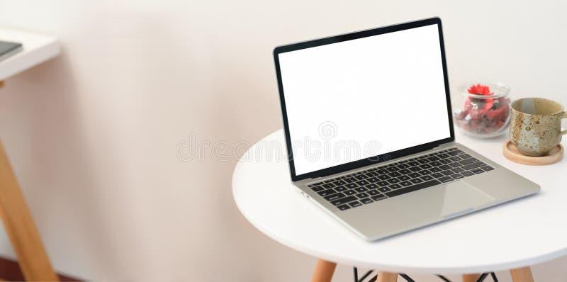 Ordenador portátil de la pantalla en blanco en la tabla de madera moderna imagen de archivo