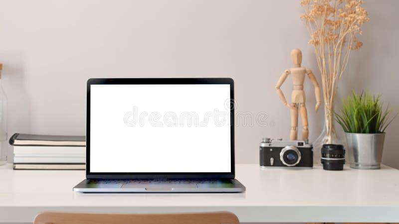 Ordenador port?til de la pantalla en blanco en la tabla de trabajo foto de archivo
