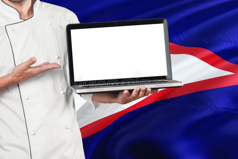 Ordenador portátil de la tenencia del cocinero con la pantalla en blanco en fondo de la bandera de American Samoa Cocine el unifo imagen de archivo