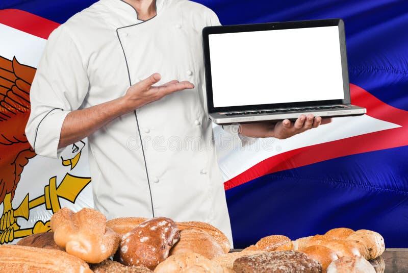 Ordenador portátil de la tenencia del panadero en la bandera de American Samoa y el fondo de los panes Uniforme que lleva del coc imagen de archivo libre de regalías