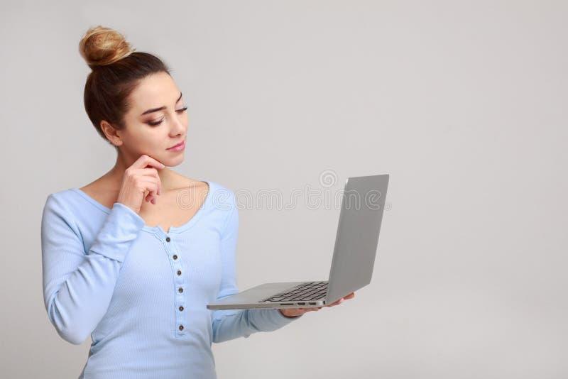Ordenador portátil de la tenencia de la mujer y Internet que practica surf en línea fotografía de archivo libre de regalías