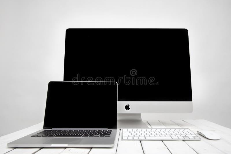 Ordenador portátil de MacBook y ordenador de iMac imagen de archivo
