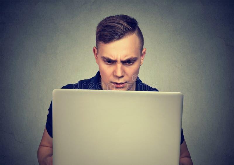 Ordenador portátil de observación del hombre confuso del trastorno foto de archivo libre de regalías