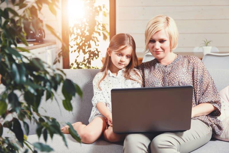Ordenador portátil de observación de las historietas de la madre y de la hija imagen de archivo libre de regalías