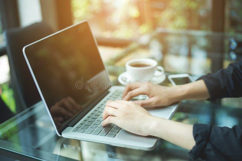 Ordenador portátil de trabajo de la mano de la mujer de negocios en oficina imagenes de archivo