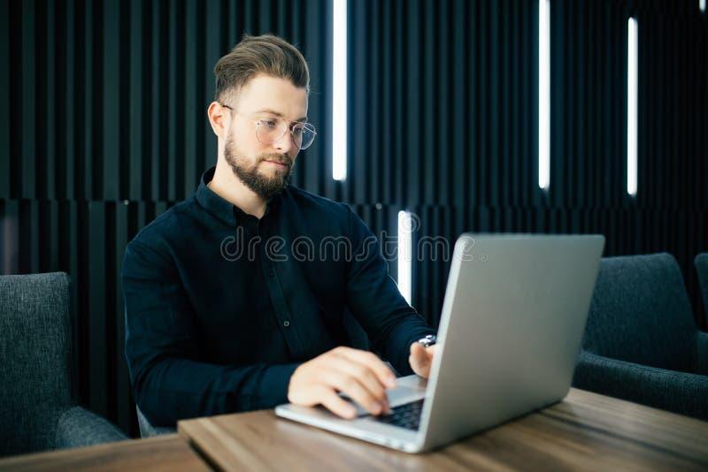 Ordenador portátil de trabajo del hombre de negocios barbudo elegante en oficina moderna Proyecto de inicio de la oficina del tra imágenes de archivo libres de regalías