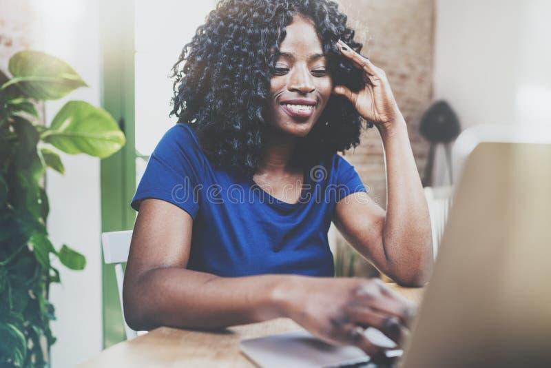 Ordenador portátil de trabajo sonriente de la mujer afroamericana mientras que se sienta en la tabla de madera en la sala de esta fotos de archivo libres de regalías