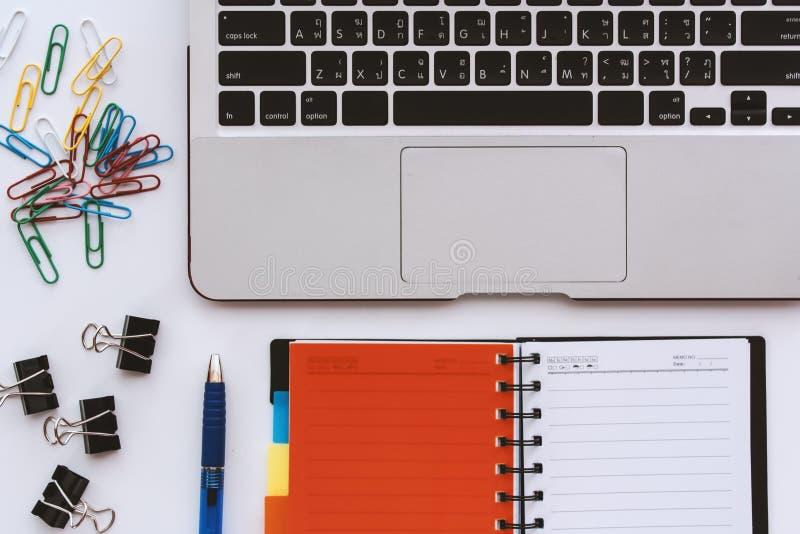 Ordenador portátil del ordenador con el cuaderno y el clip de papel abiertos de la oficina y pluma en el escritorio blanco imagenes de archivo