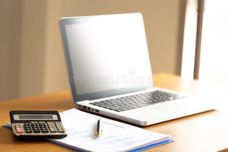 Ordenador portátil del ordenador con la carta del gráfico en la mesa de trabajo imagen de archivo