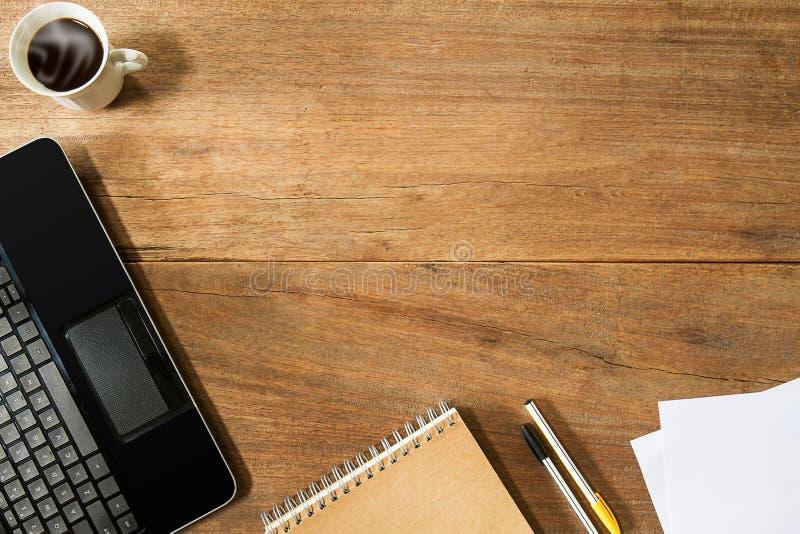 Ordenador portátil del ordenador, taza de café, cuaderno y plumas en el escritorio de madera del grunge del vintage imagen de archivo libre de regalías