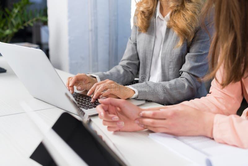 Ordenador portátil del uso de las empresarias que mecanografía en el teclado, concepto del trabajo en equipo, mujeres de negocios imagen de archivo