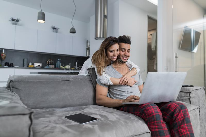 Ordenador portátil del uso de los pares junto en la sala de estar, hombre de abarcamiento sonriente feliz que se sienta en el sof fotografía de archivo libre de regalías