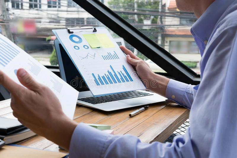 Ordenador portátil del uso del hombre de negocios con el documento del plan empresarial en el lugar de trabajo fotografía de archivo libre de regalías
