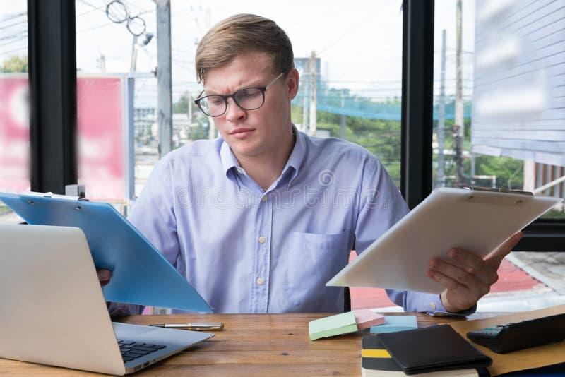 Ordenador portátil del uso del hombre de negocios con el documento del plan empresarial en el lugar de trabajo fotos de archivo libres de regalías
