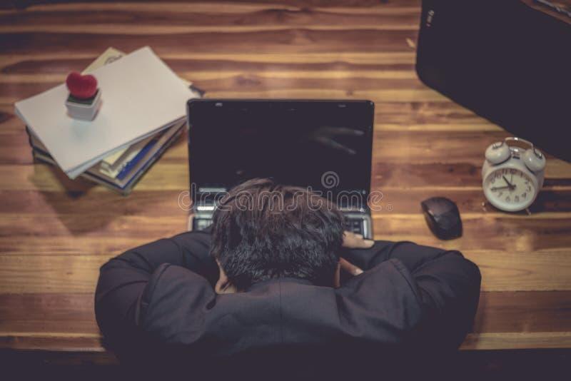 Ordenador portátil delantero el dormir del hombre de negocios imagenes de archivo