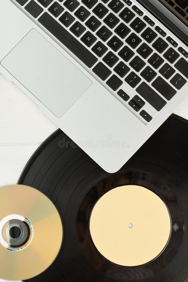 Ordenador portátil, disco de vinilo y disco compacto imágenes de archivo libres de regalías