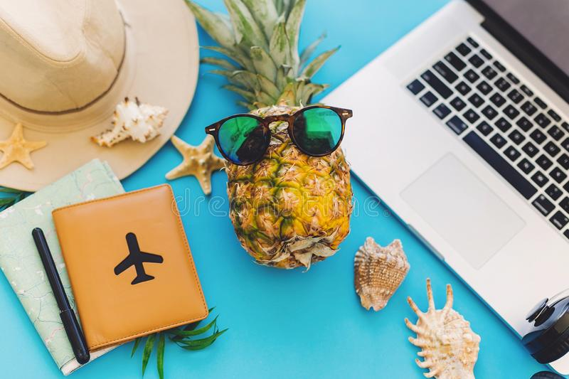 Ordenador portátil elegante, pasaporte, piña en gafas de sol, mapa, sombrero, hea imágenes de archivo libres de regalías