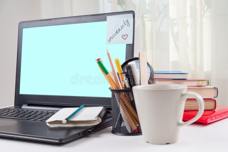 Ordenador portátil en el escritorio del ` s del estudiante, en el monitor una etiqueta engomada con la universidad de la palabra foto de archivo libre de regalías
