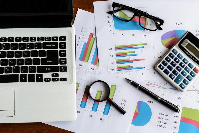 Ordenador portátil en la hoja de cálculo de la oficina del escritorio y del análisis del gráfico imagenes de archivo