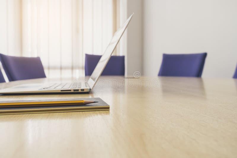 Ordenador portátil en la tabla con la sala de reunión de la reunión de la oficina de negocios de los asientos fotos de archivo libres de regalías