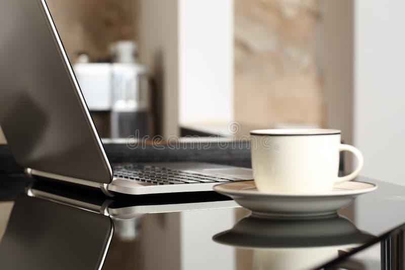 Ordenador portátil en un lugar de trabajo de la tabla con una taza de café imagen de archivo