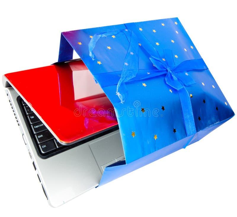 Ordenador portátil en un regalo imagenes de archivo