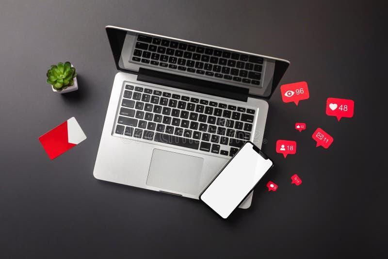Ordenador port?til en una mesa negra con una taza del caf?, de un tel?fono y de una muestra de Wi-Fi, trabajo en redes sociales fotografía de archivo