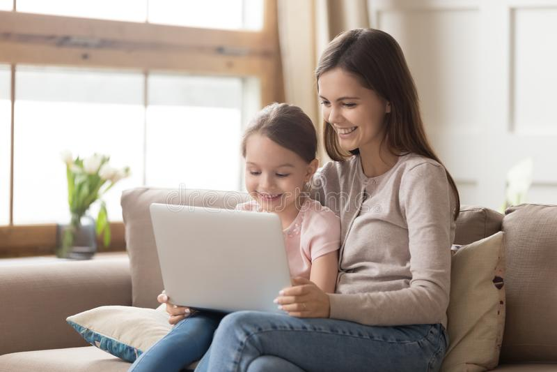 Ordenador portátil feliz del uso de la hija de la madre y del niño en casa fotos de archivo libres de regalías