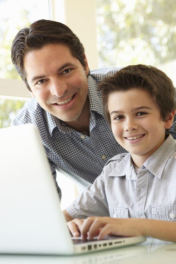 Ordenador portátil hispánico de And Son Using del padre imágenes de archivo libres de regalías